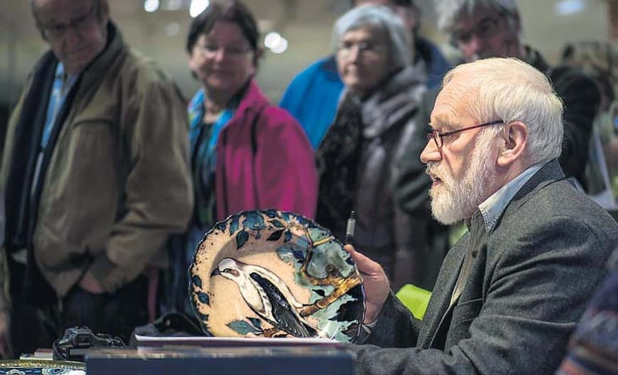 Conservator Friggo Visser taxeert een door van Jan van Schaick geschilderd wandbord van de PZH in Warenhuis Vanderveen in Assen. (Fotografie: DvhN, 23-11-2013)