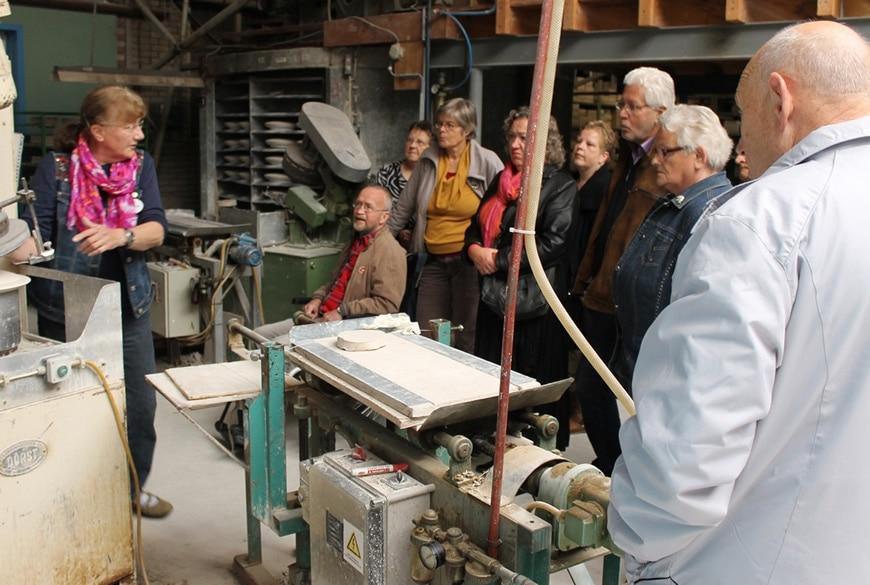 Rondleidster Yvon Kerkhoven demonstreert het werk aan de borden-persmachines.